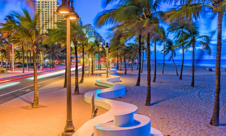 A Fort Lauderdale Beach at sunset, illuminated by street lamps