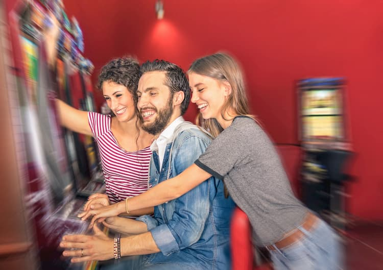 Happy young friends having fun together with slot machine