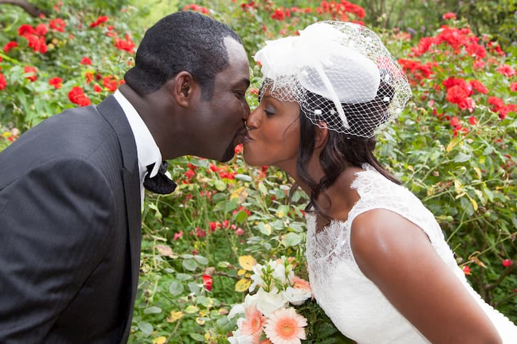 Bride and groom kissing in front of flowers in garden