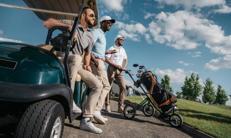 A group of men with golf clubs stand on a golf course near a golf cart