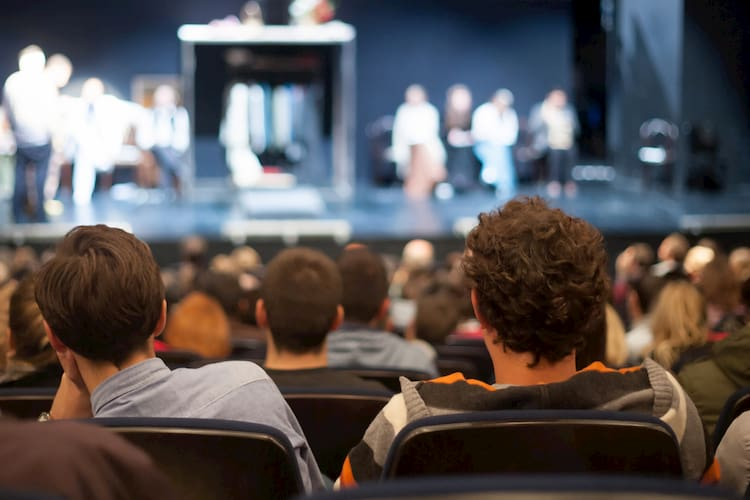 two people sit in a theatre audience and watch a show