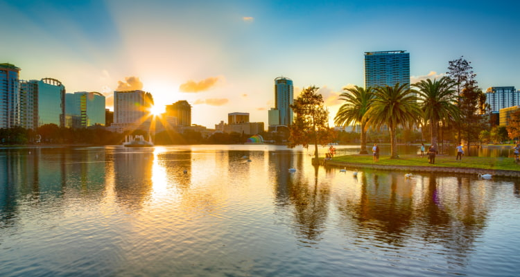 the sun sets of the Lake Eola as swans and visitors enjoy the view