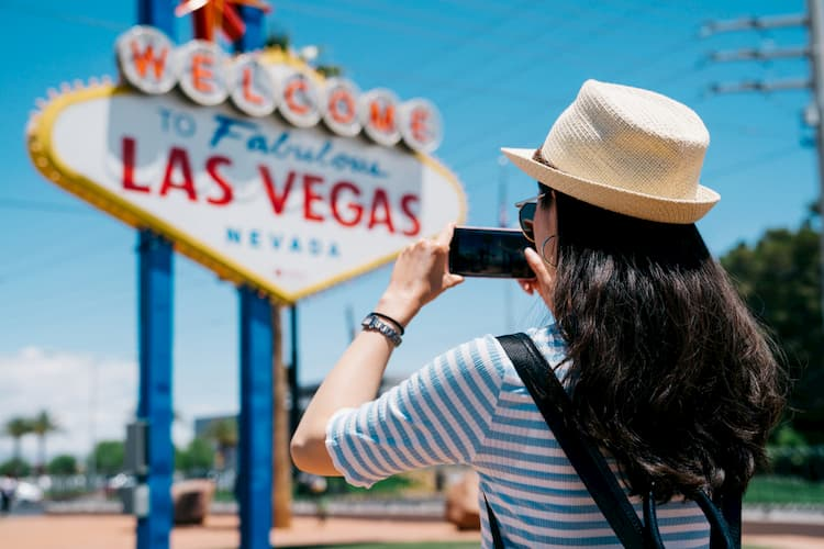 tourist taking photo of the Las Vegas city sign