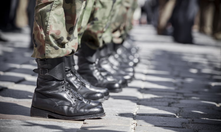 A lineup of military official's boots as they stand at attention