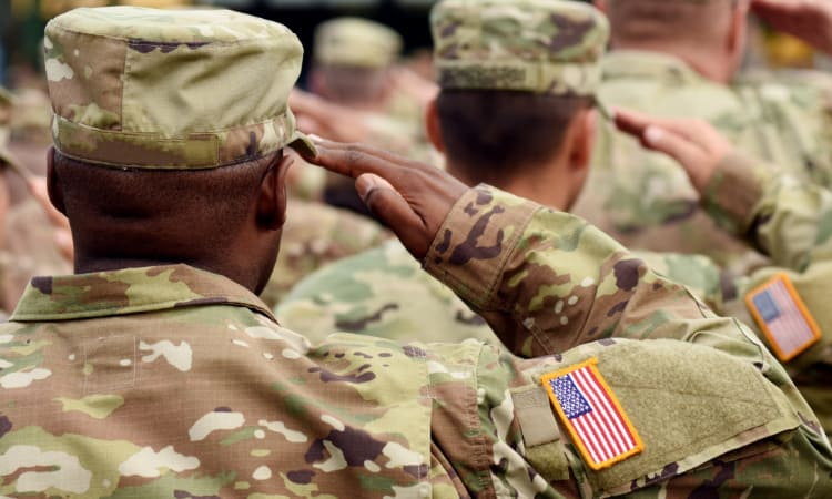A troop of soldiers in camo uniforms salute