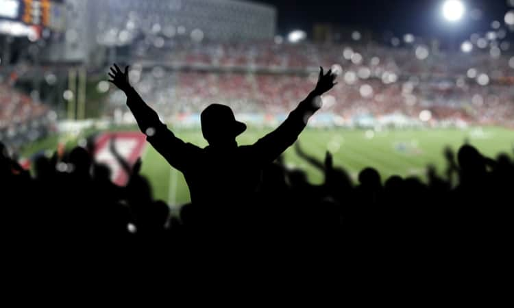 Fans cheering in the stands at a football stadium