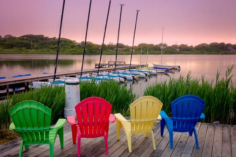 Sunset over the water in Montauk with colorful deck chairs and boats