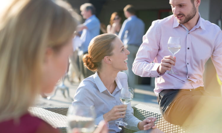 Business people in professional clothes sit in an outdoor venue, sipping drinks and networking