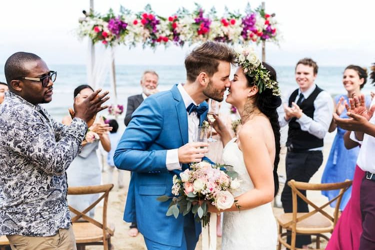 People cheering at beach wedding as couple kisses