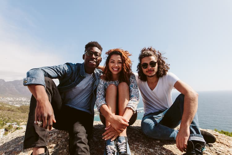 Three young people sitting on mountain