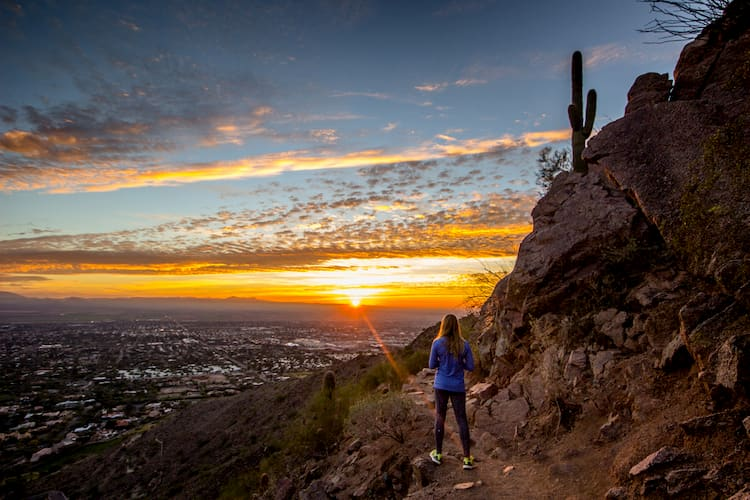 a girl stands at the edge of a hiking trail, overlooking phoenix