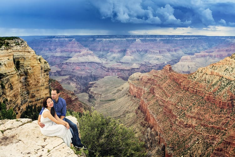 a couple smiles while sitting on the edge of the grand canyon, with vast canyons in the distance