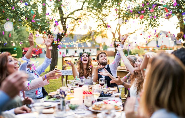 wedding guests sit at a table, laugh, and throw confetti