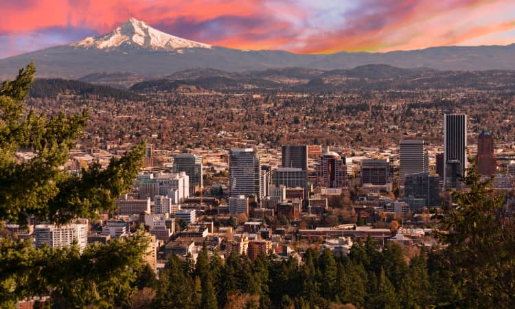 The Portland skyline at sunset, Mount Hood looming on the horizon in the far distance
