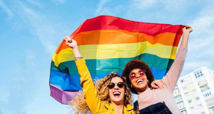 Two women embrace and raise a rainbow pride flag above their heads