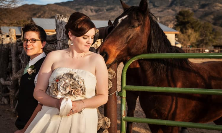 A wedding couple poses for photos on a horse ranch