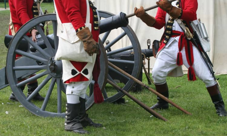 Actors in Revolutionary War garb load a cannon in a reenactment scene