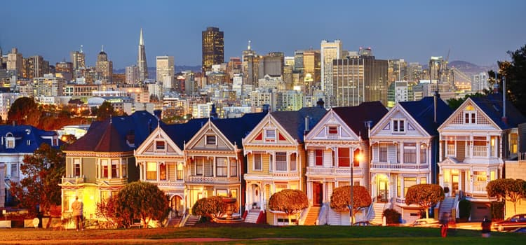 The San Francisco Painted Ladies homes with the downtown cityscape in the evening.