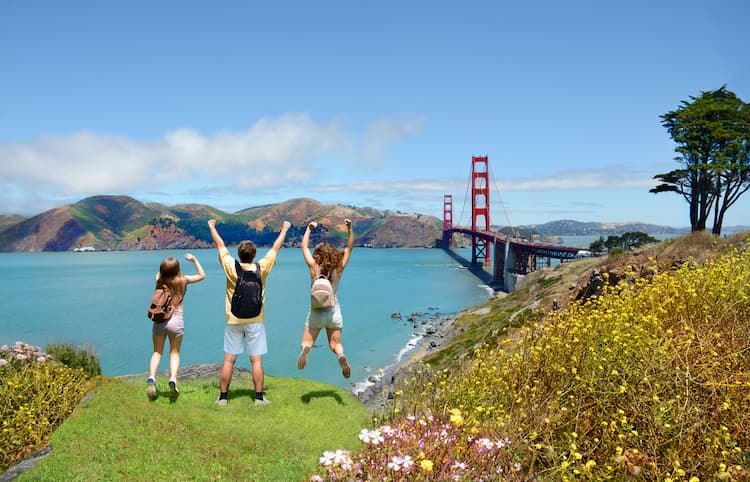 People jumping with hands up in the air and enjoying Golden Gate Bridge view
