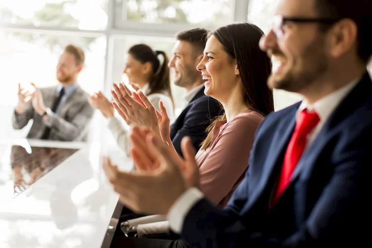 corporate event attendees in business attire clap and smile during a presentation