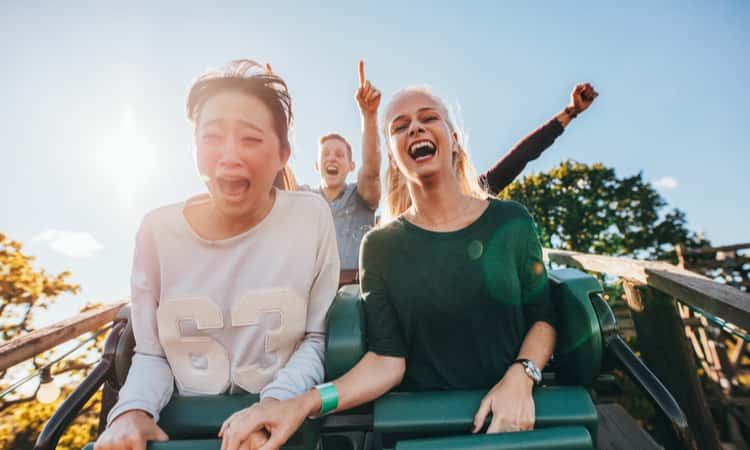 People smiling while riding a rollercoaster