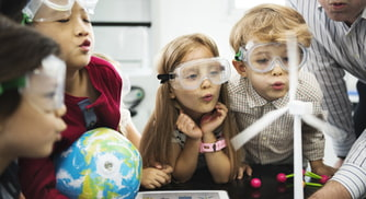 kids watch a science experiment with goggles on
