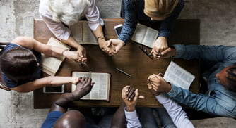 a group holds hands while they study a religious text