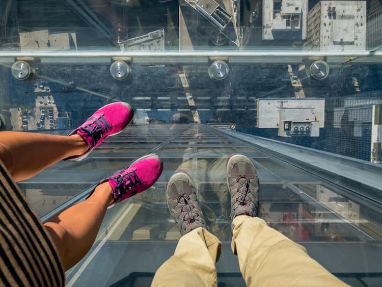 Tourists posing on a clear glass floor in a skyscraper