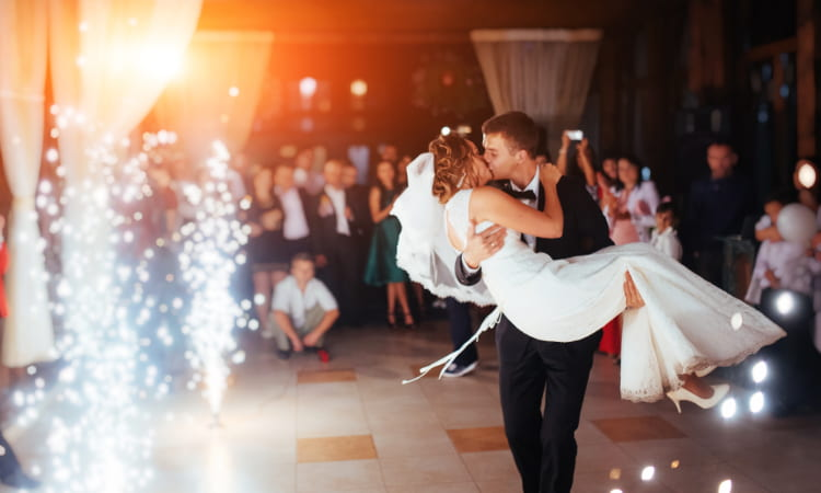 A groom carries a bride as sparklers erupt at a wedding reception