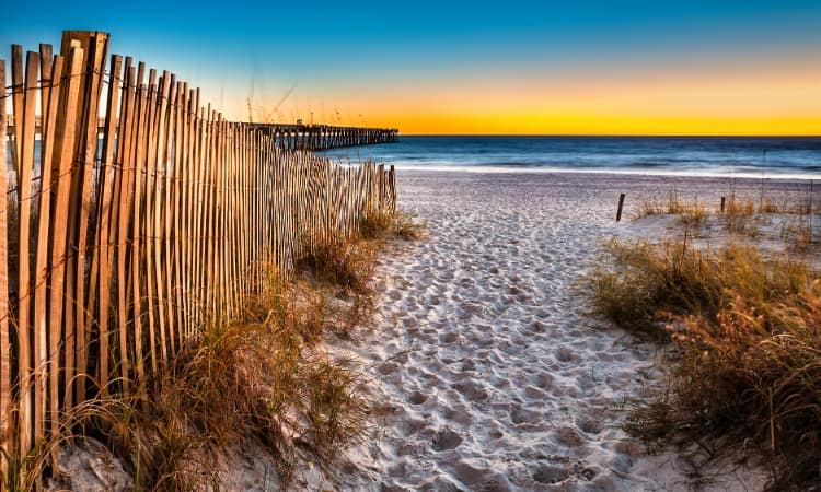The sun sets over a white sand beach in Panama City, Florida