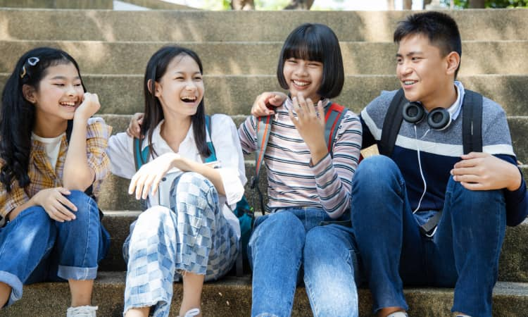 A group of college-aged teens sit and laugh on concrete steps outdoors