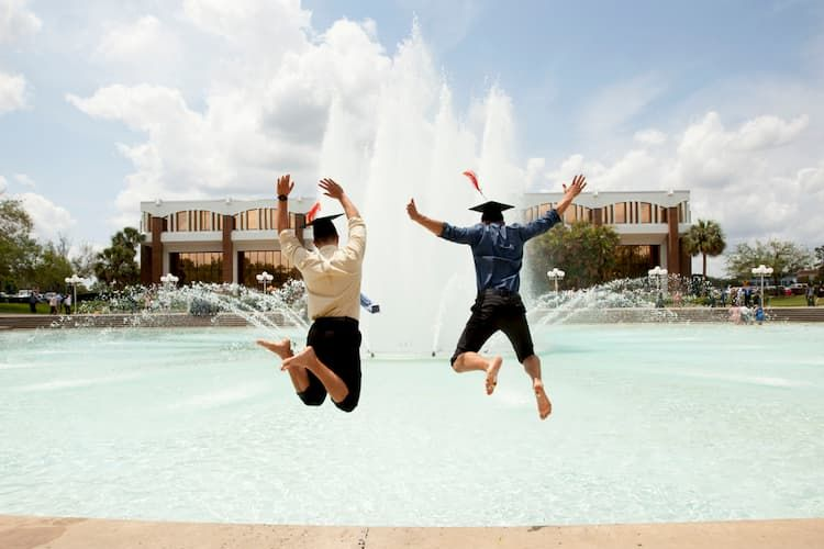 Graduates jumping into fountain at University of Central Florida