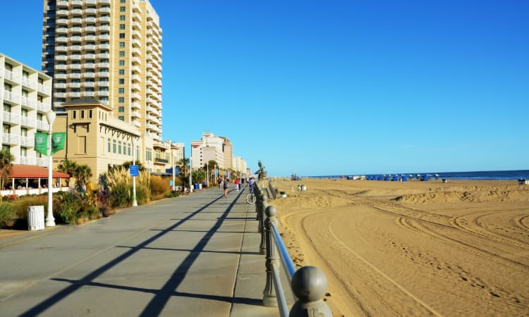 The Virginia Beach Boardwalk stretched ahead, with pedestrians and cyclists in the distance and a beach visible on the right