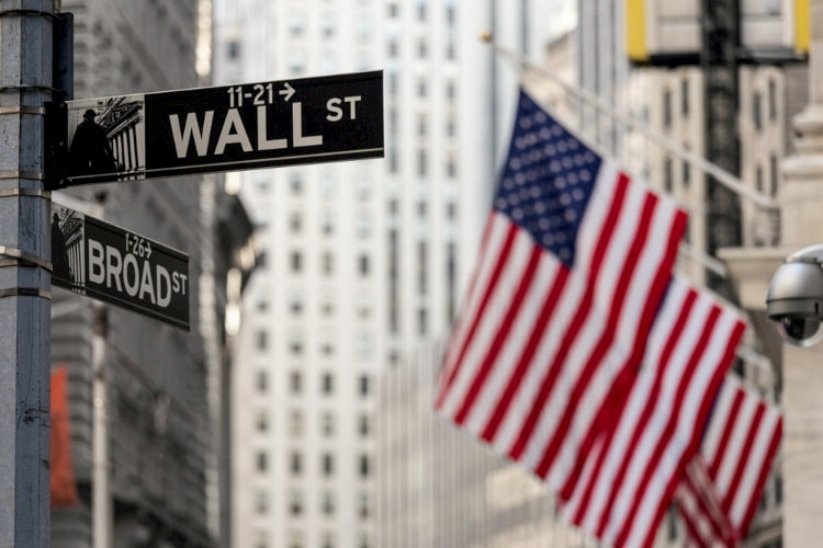 Wall street sign with the American flag in the background