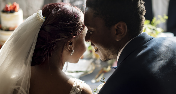 a groom whispers in his bride's ear on their wedding day