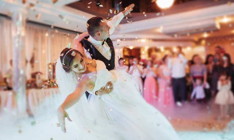 A bride and groom share their first dance in an elegant venue
