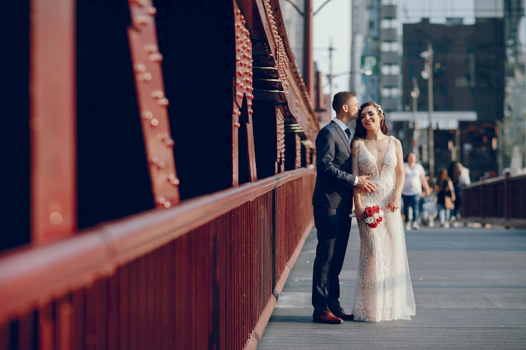 Elegant wedding couple walking in a city near bridge.