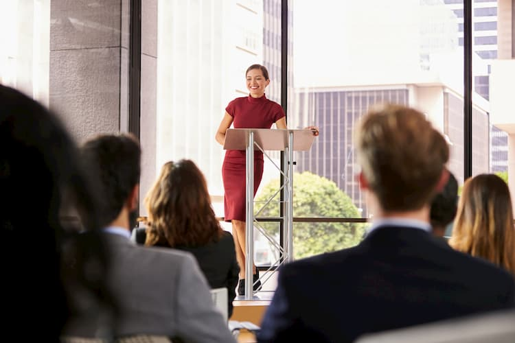 Woman in red dress speaking at podium during business conference