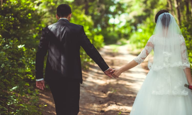 A bride and groom hold hands and walk through the woods