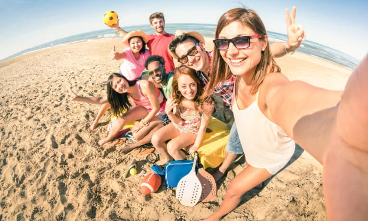 A group of young adults pose for a selfie on a beach